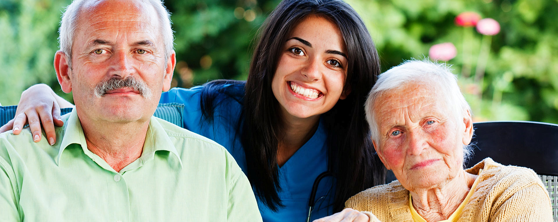 Smiling caregiver and elderly couple