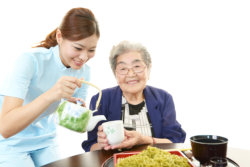 Caregiver serving foods to an elderly woman
